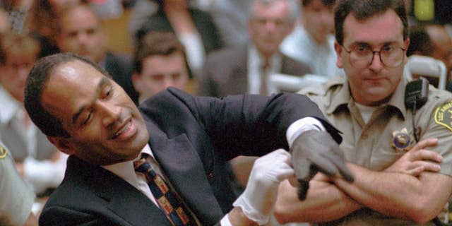 In this June 15, 1995, file photo, murder defendant, O.J. Simpson grimaces as he tries on one of the leather gloves prosecutors say he wore the night his ex-wife Nicole Brown Simpson and Ron Goldman were murdered, during the Simpson double-murder trial in Los Angeles.