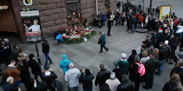 People gather at a memorial near where a bomb tore through a subway car in St. Petersburg, Russia.