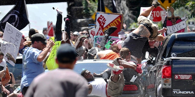 People fly into the air as a vehicle drives into a group of protesters demonstrating against a white nationalist rally in Charlottesville, Va., Saturday, Aug. 12, 2017.