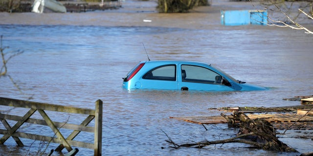 A car stands  in the floodwater at Burrowbridge, southwestern England Sunday Feb. 9, 2014. There are around 270 low-level flood alerts and 179 medium-risk warnings in place across Wales and central and southern England on Sunday. (AP Photo/Tim Ireland/PA) UNITED KINGDOM OUT