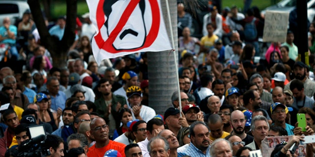 An anti-government demonstrator waves a flag against Venezuela's President Nicolas Maduro, in Caracas, Venezuela, July 31, 2017.