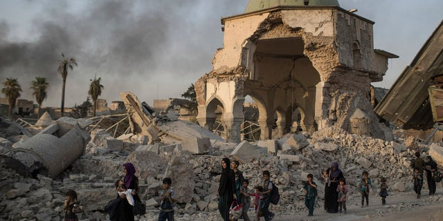 Fleeing Iraqi civilians walk past a heavily damaged al-Nuri mosque as Iraqi forces continue their advance against the Islamic State in this July 4, 2017 file photo.