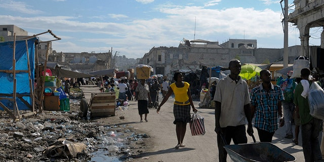 Haitians walk on a badly damaged street almost two years after the devastating January 12, 2010 earthquake that killed more than 200,000 people in Port-au-Prince December 28, 2011.