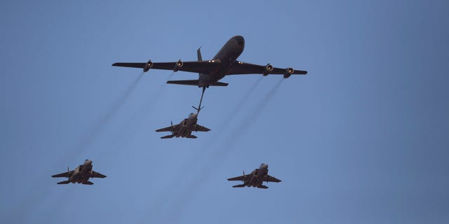 """File - In this June 27, 2013 file photo, an Israeli Air Force Boeing 707 refuels three F15I fighter jets during an acrobatics display during a graduation ceremony in the Hatzerim air force base near the southern city of Beersheba, Israel. In an apparent message to Iran, the Israeli military said Thursday, Oct. 10, 2013,  it had carried out a """"special long-range flight exercise"""". The military said its squadrons practiced refueling planes in midair this week and tested the air force's ability. The accompanying footage shows a tanker plane refueling a fighter jet midair, a key part of any long-range operation. (AP Photo/Ariel Schalit, File)"""