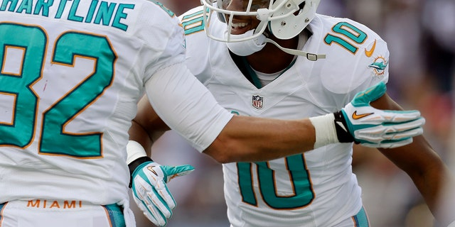 Miami Dolphins wide receiver Brandon Gibson (10) celebrates his touchdown catch against the New England Patriots with Dolphins wide receiver Brian Hartline in the first quarter of an NFL football game on Sunday, Oct. 27, 2013, in Foxborough, Mass. (AP Photo/Steven Senne)