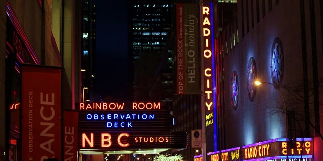 """FILE - In this Friday, Aug. 21, 2009, file photo, the NBC logo glows in neon lights among other iconic signs at its headquarters in New York. Comcast said Tuesday, Feb. 12, 2013, that it's buying General Electric's 49 percent stake in the NBCUniversal joint venture for $16.7 billion several years early, as the company takes advantage of low borrowing costs and what CEO Brian Roberts called a """"very attractive price.""""  (AP Photo/Bebeto Matthews, File)"""