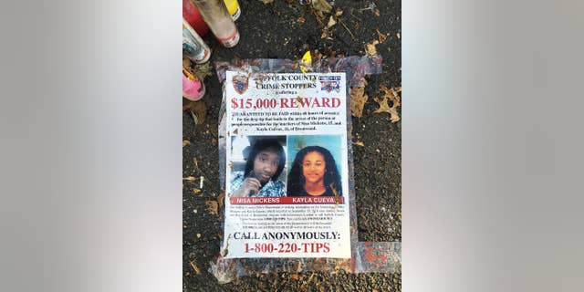 A poster featuring photos of Nisa Mickens and Kayla Cueva, part of a memorial near the spot where their bodies were found in Brentwood.
