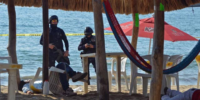 FILE - In this Jan. 6, 2017 file photo, state police inspect the site where two men were shot at the Tamarindos beach in the port city of Acapulco, Mexico. Mexico has surpassed 2,000 murders in a month for the first time since the summer of 2011, and had more murders in the first quarter of 2017 than in the start of any year in at least two decades, according to data released Friday, April 20, 2017. (AP Photo/Bernandino Hernandez, File)