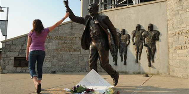 July 18, 2012: Kim Ranck touches the arm on the Joe Paterno statue as she walks away in tears.