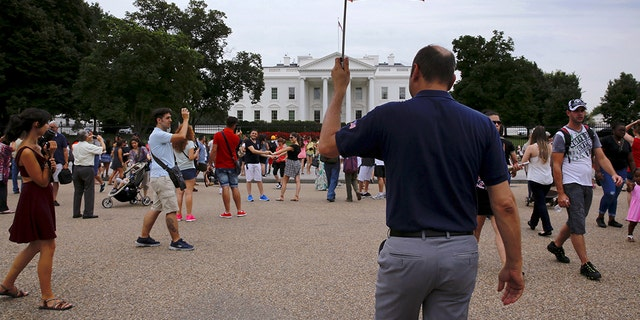 Tour guide David Machado uses a U.S. flag-themed umbrella to stay visible to his tour group as they visit the White House in Washington, August 2015