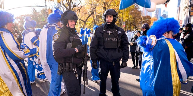 New York Police Department officers hold their position as parade participants walk around them during the Macy's Thanksgiving Day Parade in New York on Thursday, Nov. 23, 2017. This year's procession has been redesigned because of the coronavirus pandemic. (AP Photo/Craig Ruttle)