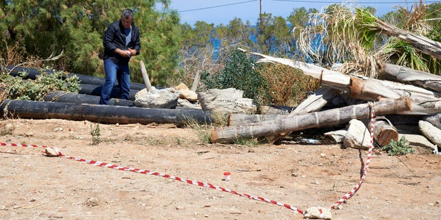 A plain clothed police officer investigates an area where a 12-year-old Russian boy was found wounded in the holiday resort of Hersonissos, on the Greek island of Crete on Wednesday, May 15, 2013. Greek authorities say the boy vacationing on the island of Crete has been found stabbed multiple times and is being airlifted to Athens for treatment of serious injuries. Police have detained a 20-year-old Dutch man who was employed at the child's hotel. (AP Photo/Bastian Parschau)