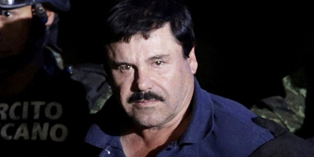 """Recaptured drug lord Joaquin """"El Chapo"""" Guzman is escorted by soldiers at the hangar belonging to the office of the Attorney General in Mexico City, Mexico January 8, 2016."""