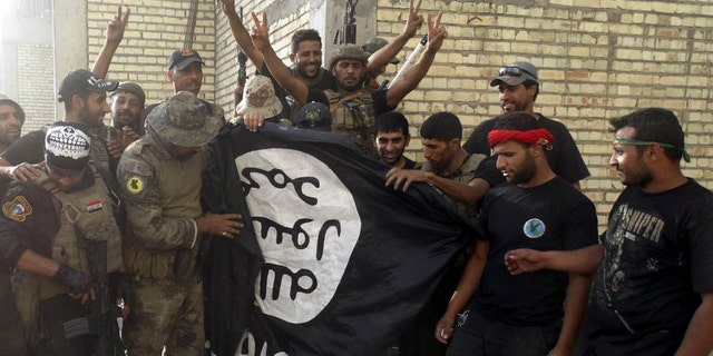 Iraqi security forces pose with ISIS flag which they pulled from University of Anbar on July 26, 2015. Forces clashed with ISIS militants inside the compound.