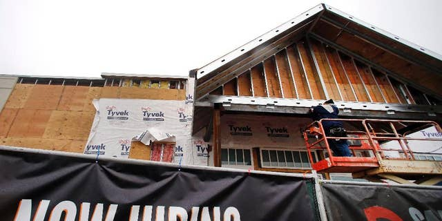 FILE - In this Jan. 12, 2015 file photo, a now hiring sign hangs nearby as a builder works on a commercial property under construction in Peabody, Mass. The Labor Department reports on state unemployment rates for December on Tuesday, Jan. 27, 2015.  (AP Photo/Elise Amendola, File)
