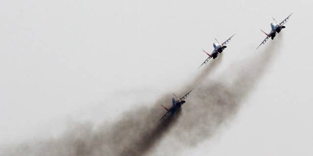 FILE - In this Sept 1, 2012 file photo, a Mig-29 jet fighters of Russian aerobatic team Strizhi (Swifts) perform during air-show in Batajnica, military airport near Belgrade, Serbia. NATO is holding an emergency exercise drill in Montenegro while Russia's troops will participate in a war game in Serbia as the two Balkans neighbors that seem to be heading different directions strategically. (AP Photo/Darko Vojinovic, File)