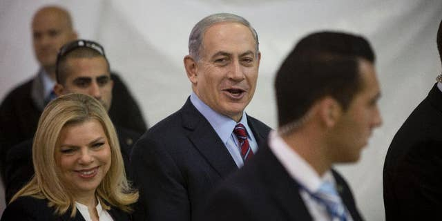 FILE - In this Wednesday, Dec. 31, 2014 file photo, Israeli Prime Minister Benjamin Netanyahu and his wife Sarah arrive for the Likud party primary elections in Jerusalem.  Israel's attorney general has ordered a criminal investigation into excessive spending at Netanyahu's residences. The announcement followed a report by the state comptroller, an official watchdog body, that cited large sums of public money spent on food, furniture, cleaning and gardening at Netanyahu and his wife's official residence in Jerusalem and their private home in the exclusive coastal city of Caesarea. (AP Photo/Oded Balilty, File)