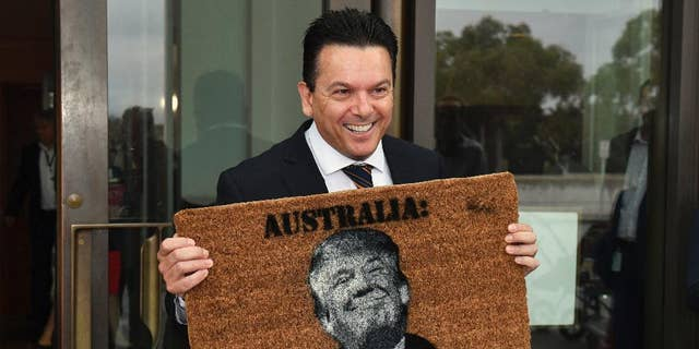 Australian Senator Nick Xenophon arrives at the Senate entrance at Parliament House in Canberra, holding a doormat featuring an image of United States President Donald Trump, Tuesday, Feb. 7, 2017. (Mick Tsikas/AAP Image via AP)