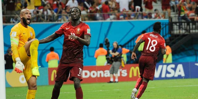United States' goalkeeper Tim Howard, left, stands near the post as he reacts next to Portugal's Eder, second from left, after Portugal's Silvestre Varela, right, scored the equaliser during the group G World Cup soccer match between the USA and Portugal at the Arena da Amazonia in Manaus, Brazil, Sunday, June 22, 2014. (AP Photo/Paulo Duarte)