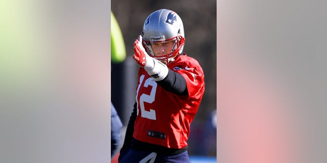 New England Patriots quarterback Tom Brady (12) gestures the direction of a route he wants run during a stretching and drills session before practice begins  at the NFL football team's facility in Foxborough, Mass., Wednesday, Nov. 20, 2013. Tom Brady and the Patriots will play Peyton Manning and the Denver Broncos Sunday night in Foxborough. (AP Photo/Stephan Savoia)