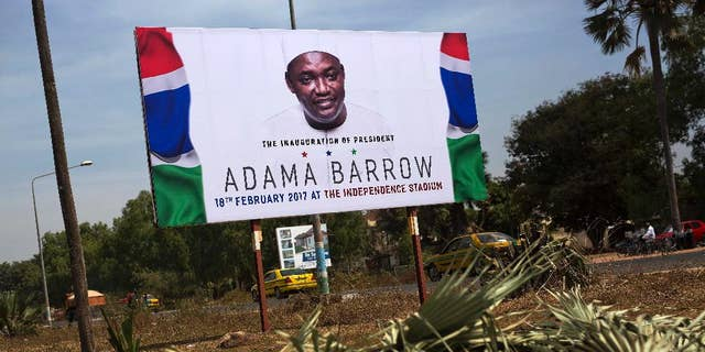 A billboard calling for the inauguration of Adam Barrow as president in Feb. 18 is set on the side of a road in Serrukunda, Gambia, Friday Jan. 27, 2017. Hundreds of thousands turned out Thursday to greet President Adama Barrow, a week after he took the oath of office in neighboring Senegal. (AP Photo/Jerome Delay)