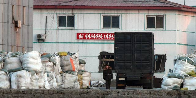 a North Korean soldier walks past a truck park near the goods pile up on a dockyard in Sinuiju, North Korea, as seen from Dandong in northeastern China's Liaoning province.