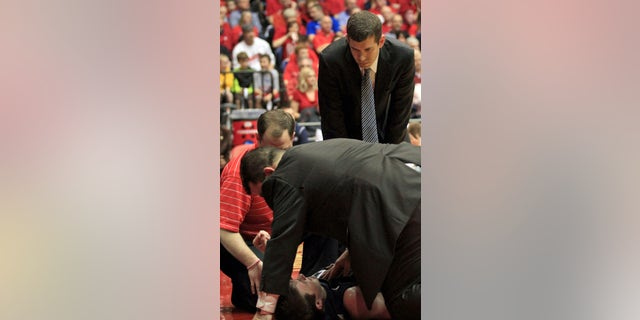 Butler head coach Brad Stevens looks on as his trainers attend to Rotnei Clarke after Clarke was injured during the first half of an NCAA college basketball game against Dayton, Saturday, Jan. 12, 2013, in Dayton, Ohio. Clarke was taken from the arena on a backboard.(AP Photo/Skip Peterson)