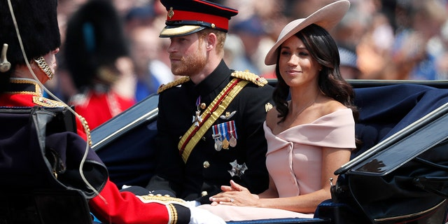 Britain's Prince Harry, left, and Meghan, Duchess of Sussex ride in a carriage to attend the annual Trooping the Colour Ceremony in London, June 9, 2018.