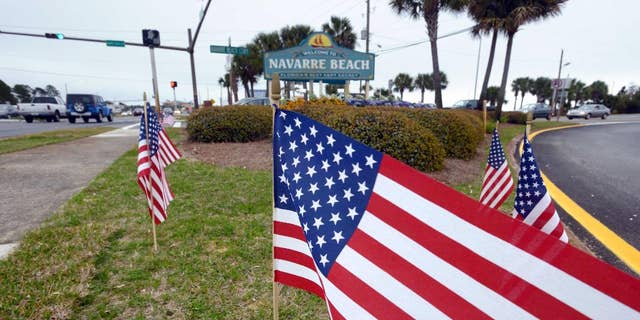 American flags stand in the median near the bridge entrance to Navarre Beach, Fla., Thursday, March 12, 2015. There's been an outpouring of support in this heavily military community following the crash of an Army Black Hawk helicopter Tuesday evening. In various parts of Navarre, 11 flags are placed, one one for each of the servicemen missing in the crash.  (AP Photo/Northwest Florida Daily News, Devon Ravine)