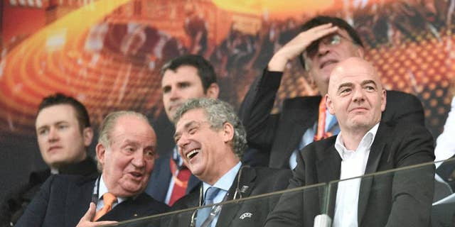 Former King Juan Carlos I of Spain, left, and FIFA president, Gianni Infantino, right, laugh as they wait for the start of the Europa League final soccer match between Liverpool and Sevilla in Basel, Switzerland, Wednesday, May 18, 2016. (AP Photo/Martin Meissner)