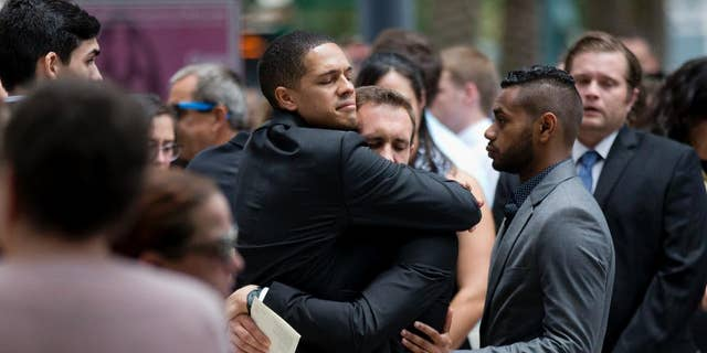 Mourners embrace after the funeral service for Christopher Leinonen.