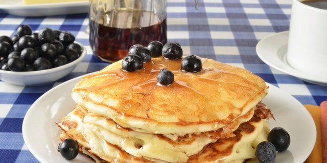 Blueberry pancakes on a picnic table with a cup of coffee