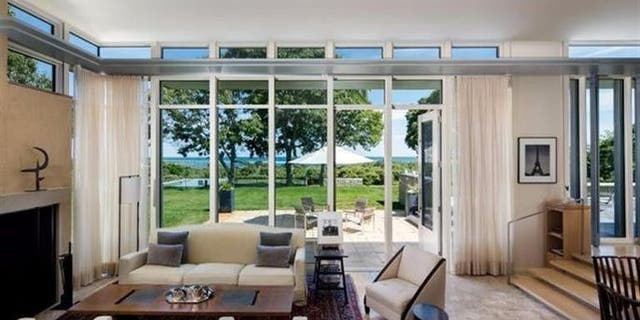 The living room boasts floor-to-ceiling windows with ocean views.