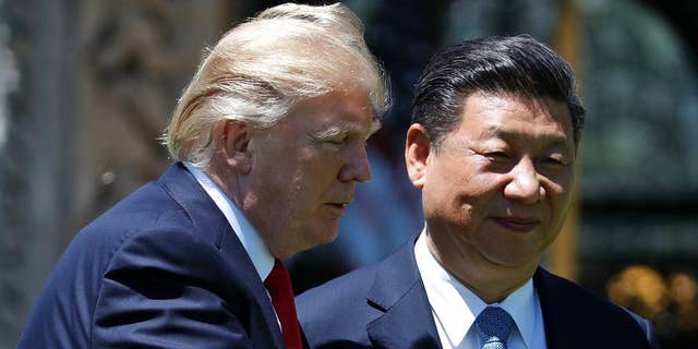 In this April 7, 2017, file photo, U.S. President Donald Trump gestures as he and Chinese President Xi Jinping walk together after their meetings at Mar-a-Lago in Palm Beach, Fla.