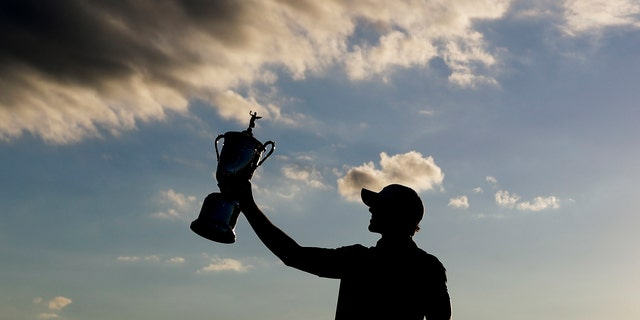 Brooks Koepka poses with the winning trophy after the U.S. Open golf tournament, June 18, 2017, at Erin Hills in Erin, Wis. (Associated Press)