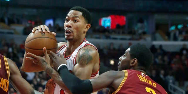 Chicago Bulls point guard Derrick Rose (1) drives past Cleveland Cavaliers point guard Kyrie Irving (2) during the second half of an NBA basketball game Monday, Nov. 11, 2013, in Chicago. The Bulls won 96-81. (AP Photo/Charles Rex Arbogast)