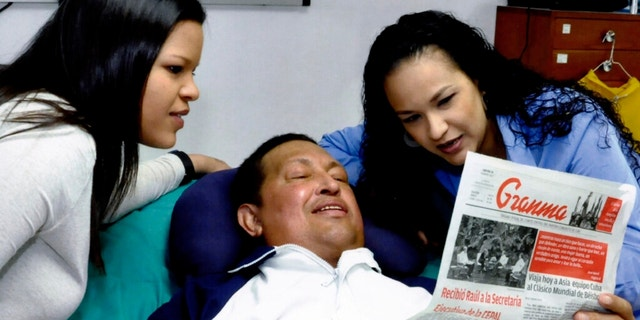 In this photo released Friday, Feb. 15, 2013 by Miraflores Presidential Press Office, Venezuela's President Hugo Chavez, center, poses for a photo with his daughters, Maria Gabriela, left, and Rosa Virginia as he holds a copy of Cuba's state newspaper at an unknown location in Havana, Cuba, Thursday, Feb. 14, 2013. Chavez remains in Havana undergoing unspecified treatments following his fourth cancer-related operation on Dec. 11. He has hasn't been seen or spoken publicly in more than two months. (AP Photo/Miraflores Presidential Press Office)