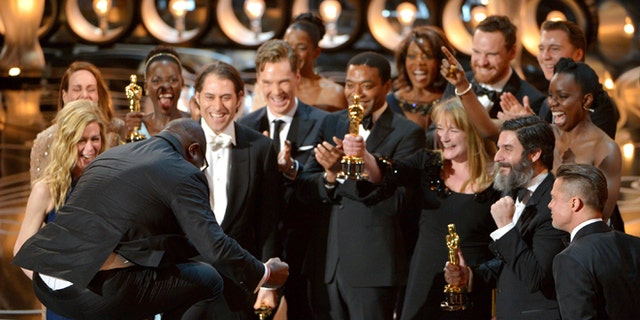 """March 2, 2014: Director Steve McQueen, left, celebrates with the cast and crew of """"12 Years a Slave"""" as they accept the award for best picture during the Oscars at the Dolby Theatre in Los Angeles."""
