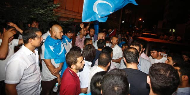Uighurs living in Turkey and Turkish supporters, some carrying flags of East Turkestan, the term separatist Uighurs and Turks use to refer to the Uighurs homeland in China's Xinjiang region, gather outside the Thai consulate in Istanbul, early Thursday, July 9, 2015. A group of protesters stormed the consulate overnight, smashing windows and breaking into the offices (AP Photo)