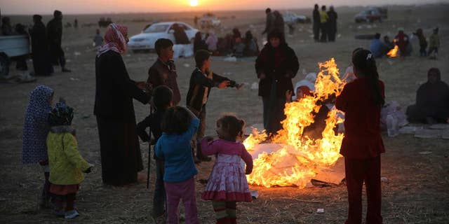 Nov. 17, 2016: Iraqis, who fled the fighting between Iraqi forces and Islamic State militants, gather around flames to warm themselves from the cold, as they wait to cross to the Kurdish controlled area, in the Nineveh plain, northeast of Mosul.