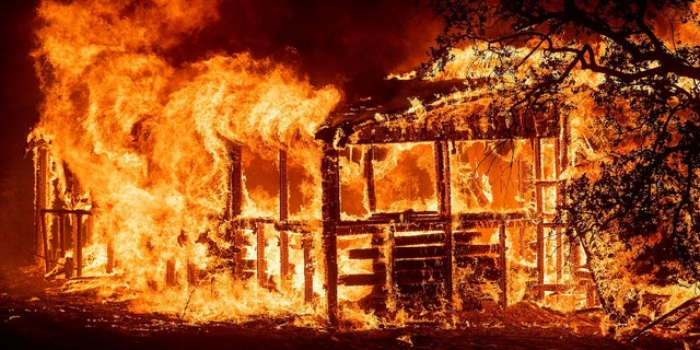 A structure burns as the Carr Fire races along Highway 299 near Redding, Calif., on Thursday, July 26, 2018.