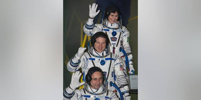 File photo - U.S. astronaut Terry Virts, centre, Russian cosmonaut Anton Shkaplerov, bottom, and Italian astronaut Samantha Cristoforetti, crew members of the mission to the International Space Station, ISS, gesture prior the launch of Soyuz-FG rocket at the Russian leased Baikonur cosmodrome, Kazakhstan, Monday, Nov. 24, 2014.