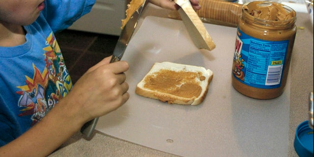 ** ADVANCE FOR TUESDAY, JULY 12 **   Nick, 7, makes a peanut butter sandwich to go in his lunch Monday, June 22, 2005 in St. Louis. Nick's mom Sherry Claxton, a licensed dietician, lets her three kids make their own lunches butkeeps a close eye on what goes in them.(AP photo/Tom Gannam)