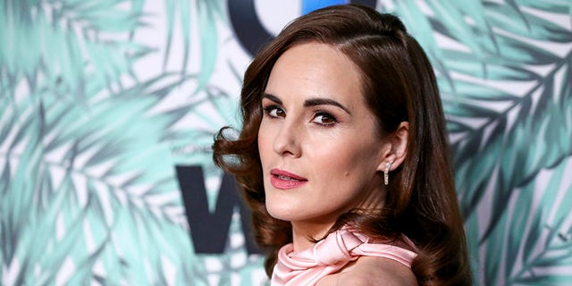 FILE - In this Feb. 24, 2017, file photo, Michelle Dockery arrives at the 10th Annual Women in Film Pre-Oscar Cocktail Party at Nightingale Plaza in Los Angeles. Filming has begun for the 'Downton Abbey' movie. Dockery, who plays Lady Mary in the global hit, posted a photo on Instagram with the caption, 'And...we're off.'