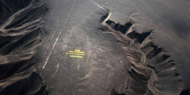 """Greenpeace activists stand next to massive letters delivering the message """"Time for Change: The Future is Renewable,"""" next to the hummingbird geoglyph in Nazca in Peru, Monday, Dec. 8, 2014. Greenpeace activists from Brazil, Argentina, Chile, Spain, Germany, Italy and Austria displayed the message, which can be viewed from the sky, during the climate talks in Peru, to honor the Nazca people, whose ancient geoglyphs are one of the country's cultural landmarks. (AP Photo/Rodrigo Abd)"""