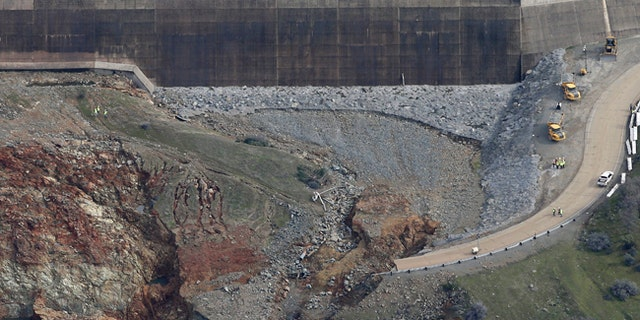 Erosion caused when overflow water cascaded down the emergency spillway, right, of the Oroville Dam in California.