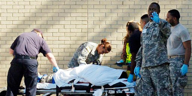 In this Thursday, Nov. 6, 2009 photo, emergency personnel transport an unidentified soldier from the Soldier Readiness Center following a shooting at Fort Hood, Texas.  Authorities said Maj. Nidal Malik Hasan went on a shooting spree Thursday at the sprawling Texas post, killing at least 12 people and injuring dozens more.  (AP Photo/Killeen Daily Herald, David Morris)