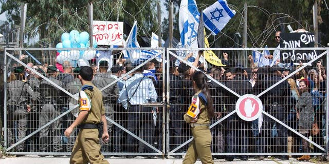 FILE - In this Tuesday, March 29, 2016 file photo, Israeli right wing protesters wave flags outside of Castina Military Court near the southern Israeli city of Ashkelon. Israel's military justice system is in the spotlight as it investigates an Israeli soldier caught on tape shooting to death a subdued Palestinian attacker, a case that has gripped and polarized the nation. While the military has stressed the independence of its courts, critics say the system's poor track record for punishing errant soldiers is perpetuating a culture of impunity that allows allegedly improper conduct to recur.  (AP Photo/Ariel Schalit, File)