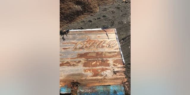 """Photos posted by the Coast Guard shows pieces of a wooden boat that has the name """"Rio"""" and """"Barca"""" on it."""