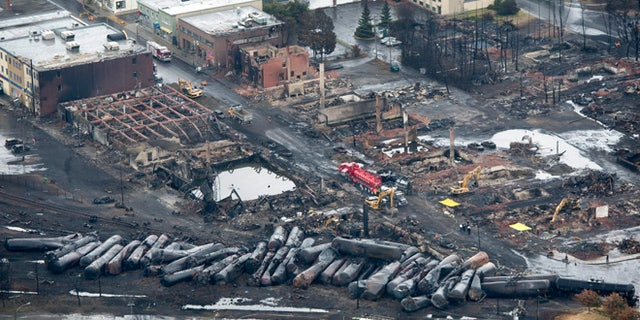 This aerial photo, workers comb through the debris after a train derailed causing explosions of railway cars carrying crude oil Tuesday, July 9, 2013 in Lac-Megantic, Quebec, Canada on Tuesday July 9, 2013.  At least thirteen people were confirmed dead and nearly 40 others were still missing in a catastrophe that raised questions about the safety of transporting oil by rail instead of pipeline.  (AP Photo/ The Canadian Press, Paul Chiasson)